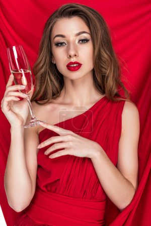 Photo for Attractive girl posing in red dress with glass of champagne - Royalty Free Image