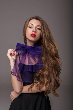 attractive elegant woman with long hair posing in purple scarf, isolated on grey