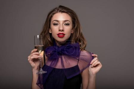attractive girl posing with champagne glass, isolated on grey