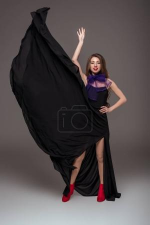 beautiful girl posing in black dress and purple scarf for fashion shoot, isolated on grey