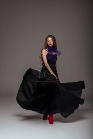 beautiful girl posing in black dress for fashion shoot, on grey