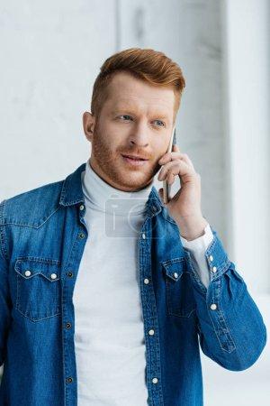 Handsome bearded man talking on phone by window