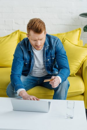 Man with credit card and laptop making online payment