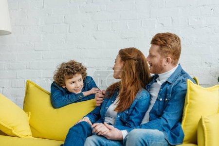 Photo for Parents sitting on sofa and looking at smiling son - Royalty Free Image