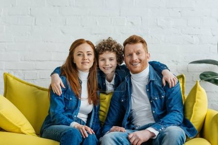 Hugging son and parents sitting on sofa