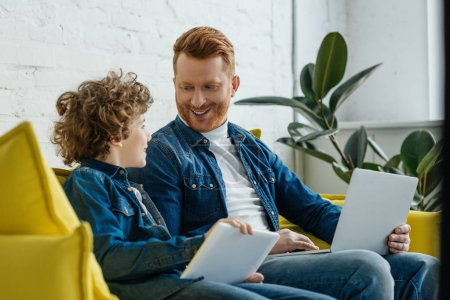 Smiling father with son using tablet and laptop