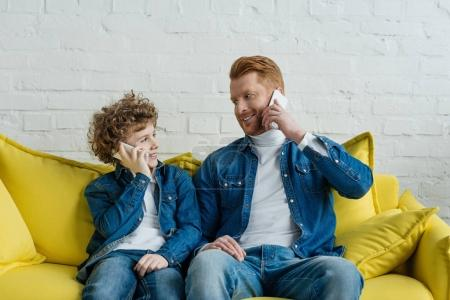 Photo for Father and son talking on smartphones while sitting on sofa - Royalty Free Image