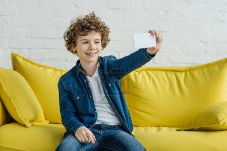 Photo pour Petit enfant souriant prenant selfie assis sur le canapé - image libre de droit