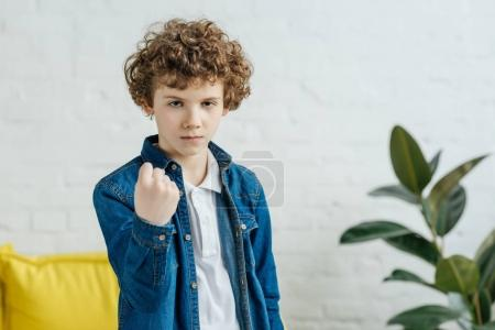 Angry child boy showing clenched fist