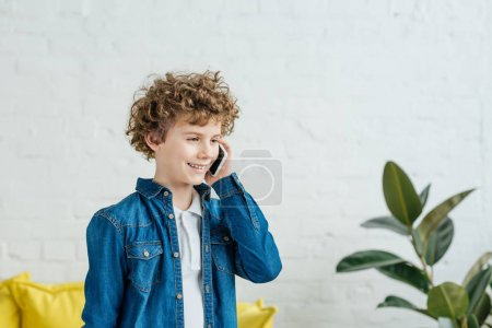 Little child boy with curly hair talking on the phone