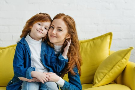 Redhead woman embracing her daughter on sofa