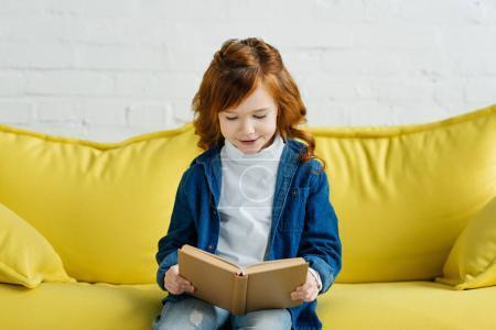 Photo pour Enthousiaste petit livre de lecture pour enfants sur canapé - image libre de droit