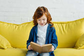 Enthusiastic little child reading book on sofa