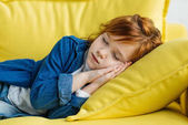 Little child with red head sleeping on sofa