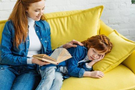 Sleepy little child listening to mother reading book