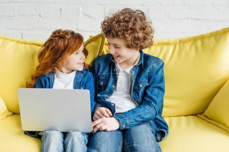 Photo pour Enfants mignons utilisant un ordinateur portable tout en étant assis sur le canapé - image libre de droit