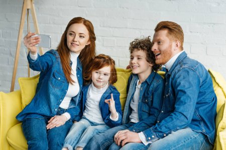 Redhead smiling family taking selfie while sitting on sofa