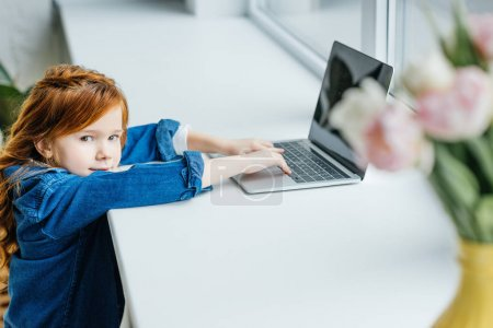 Little redhead child using laptop on windowsill
