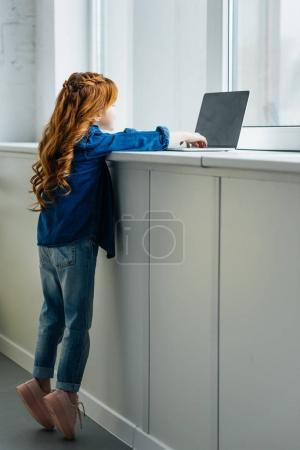 Adorable child reaching to laptop on windowsill