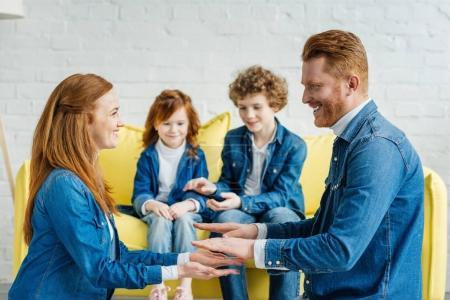 Parents having fun while children sitting on sofa