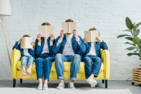 Photo for Family sitting on sofa and holding books - Royalty Free Image