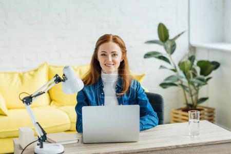 Smiling businesswoman looking at camera by laptop at home office