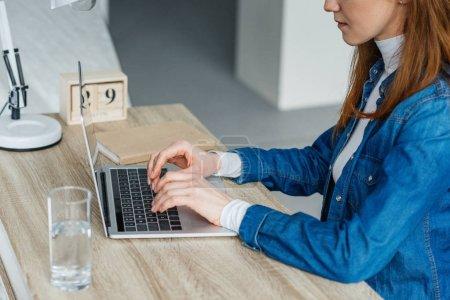Photo pour Femme, tapant sur l'ordinateur portable à la table de travail - image libre de droit