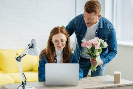 Man gifting young woman working by laptop with a bouquet of flowers