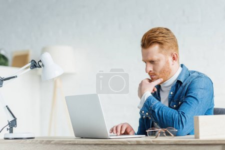 Thoughtful young man looking at laptop screen