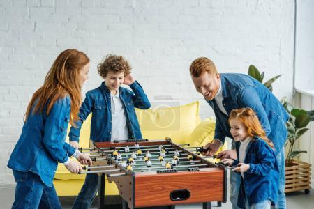 Happy family having fun while playing foosball
