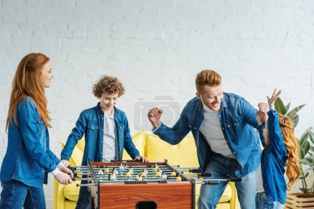 Children and parents playing table football together