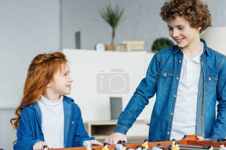 sister and brother playing foosball game
