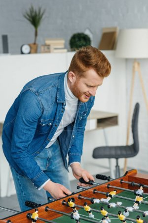Photo for Redhead young man playing table football - Royalty Free Image