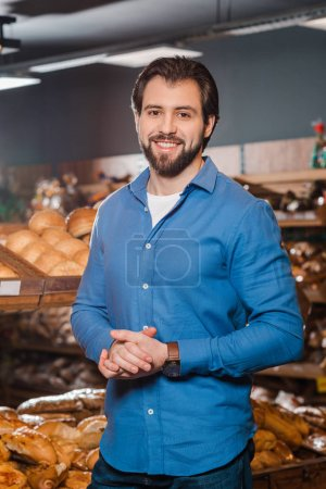 portrait of smiling man looking at camera in supermarket