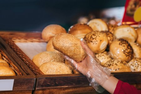 partial view of shopper choosing loaf of bread in store