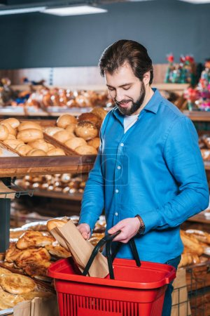 man putting loaf of bread into shopping basket in supermarket