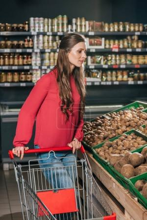 woman with shopping cart choosing raw vegetables in grocery shop