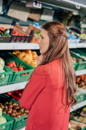side view of woman choosing fresh raw vegetables in grocery store