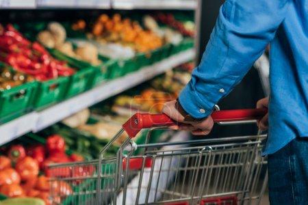 recadrée tir d'homme avec panier d'achat en épicerie