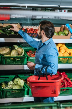 man with shopping basket choosing fresh vegetables in grocery shop