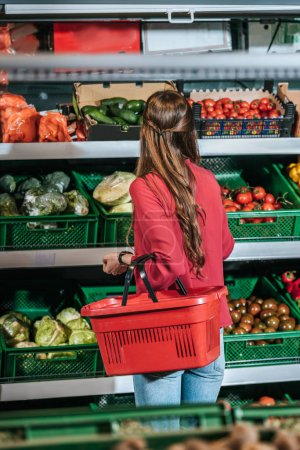 back view of woman with shopping basket choosing fresh raw vegetables in grocery store