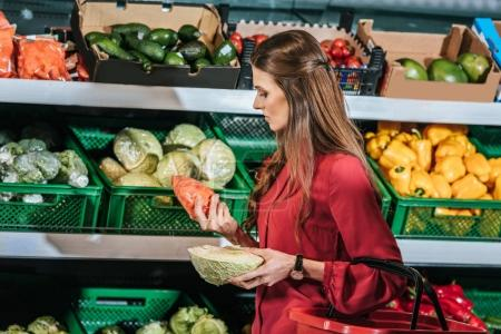 woman choosing fresh raw vegetables in grocery store
