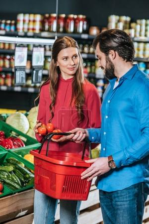 couple with shopping basket shopping together in supermarket