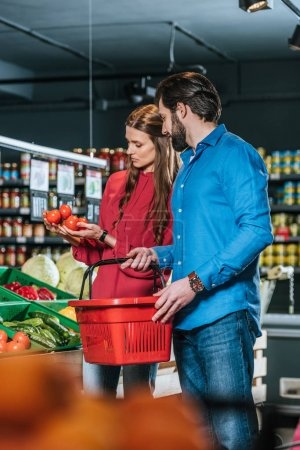couple with shopping basket choosing fresh vegetables together in supermarket