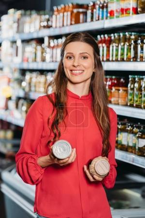 portrait of smiling woman with products in hands in hypermarket
