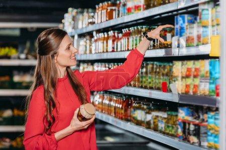 Photo pour Femme souriante, choisir des produits en hypermarché - image libre de droit