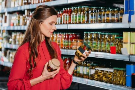 portrait of attractive woman choosing products in hypermarket