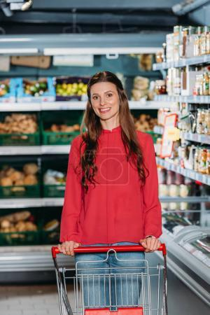 portrait of smiling woman with shopping trolley in supermarket