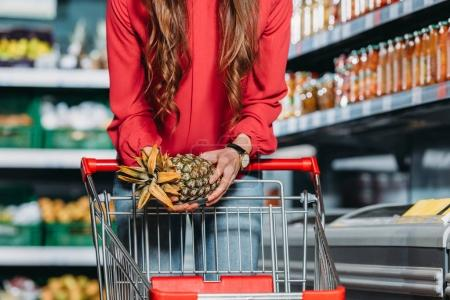cropped shot of woman putting fresh pineapple into shopping trolley in supermarket