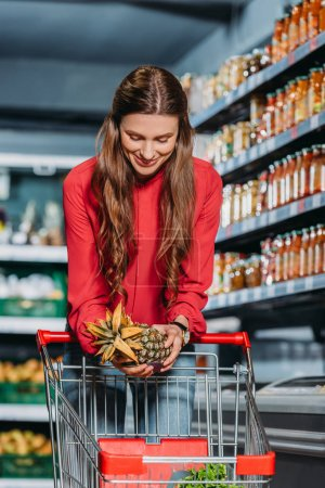 woman putting fresh pineapple into shopping trolley in supermarket